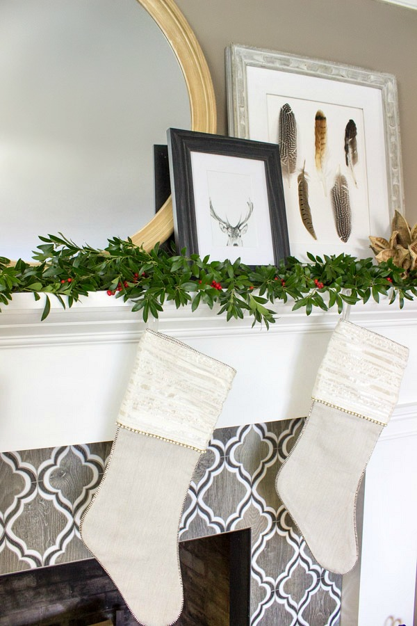 Fireplace mantel decorated for Christmas with simple greenery and berries, stockings, and a deer art print