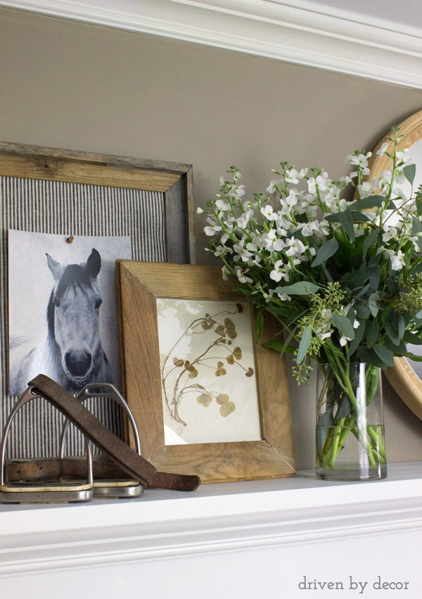 Fireplace mantel decorated with layered art, a round mirror, and flowers