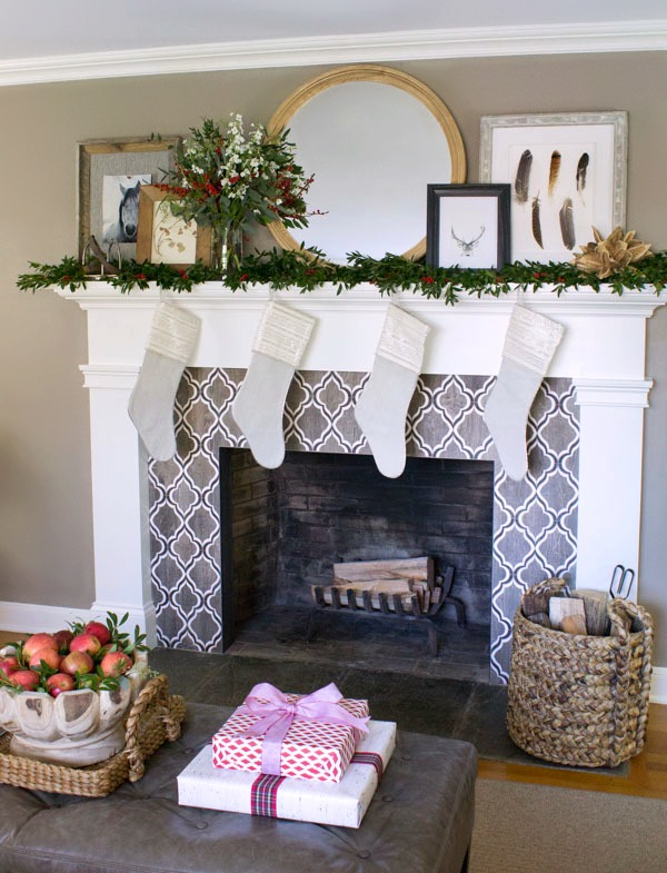 Fireplace with black, white, and wood toned geometric tile decorated for the holidays!