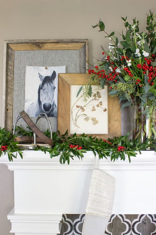 Greenery, flowers, and layered art adorn this holiday mantel