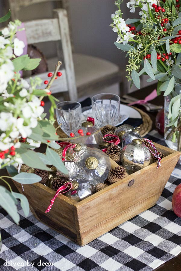 Holiday centerpiece of glass and metallic ornaments mixed with pine cones