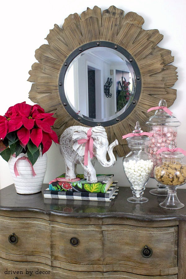 Our foyer chest decorated for the holidays with apothecary jars filled with goodies!