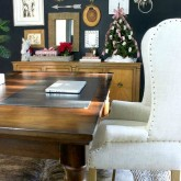 Our home office decorated for the holidays - gallery wall, wrapped gifts, advent tree, World Market table, cowhide rug, jute rug, and wingback chair