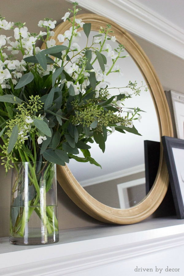Round wood mirror on fireplace mantel