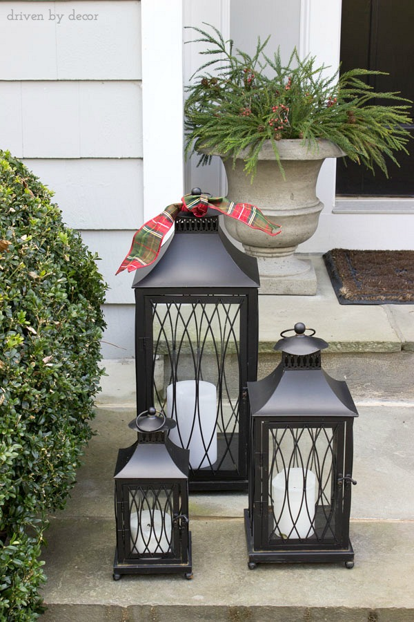 Simple holiday decorations for your front porch - a set of lanterns adorned with holiday ribbon and urns filled with greenery and berries