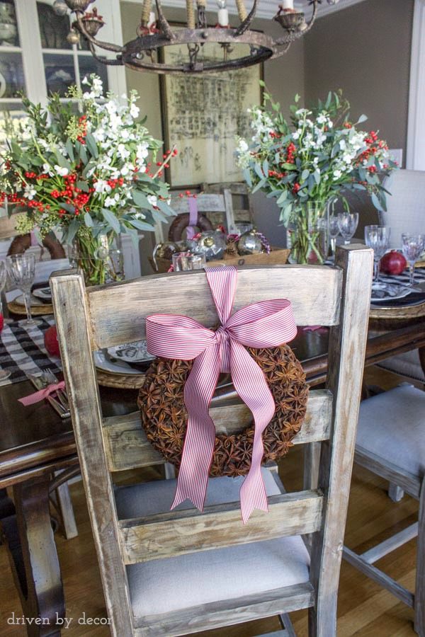Star anise wreaths tied onto the back of dining chairs are part of this festive holiday table
