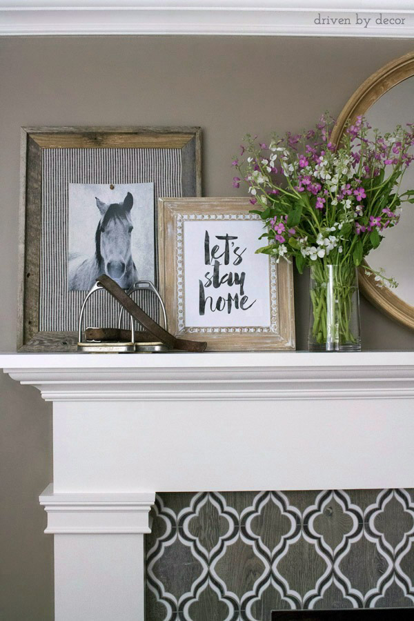 Loving this arrangement of art on the fireplace mantel with a round mirror in the middle and layered, framed art and flowers