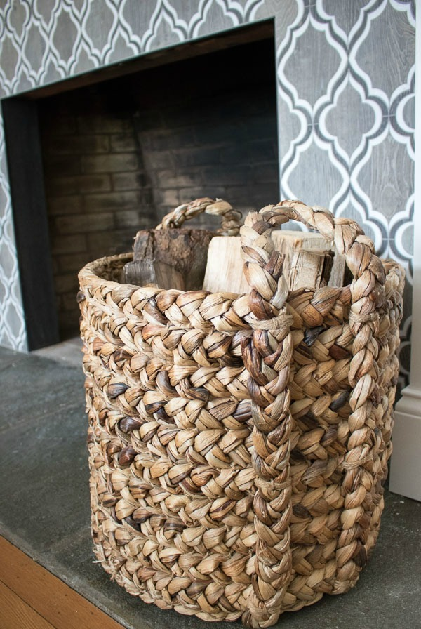 A large woven basket used to store extra firewood by the fireplace - love!