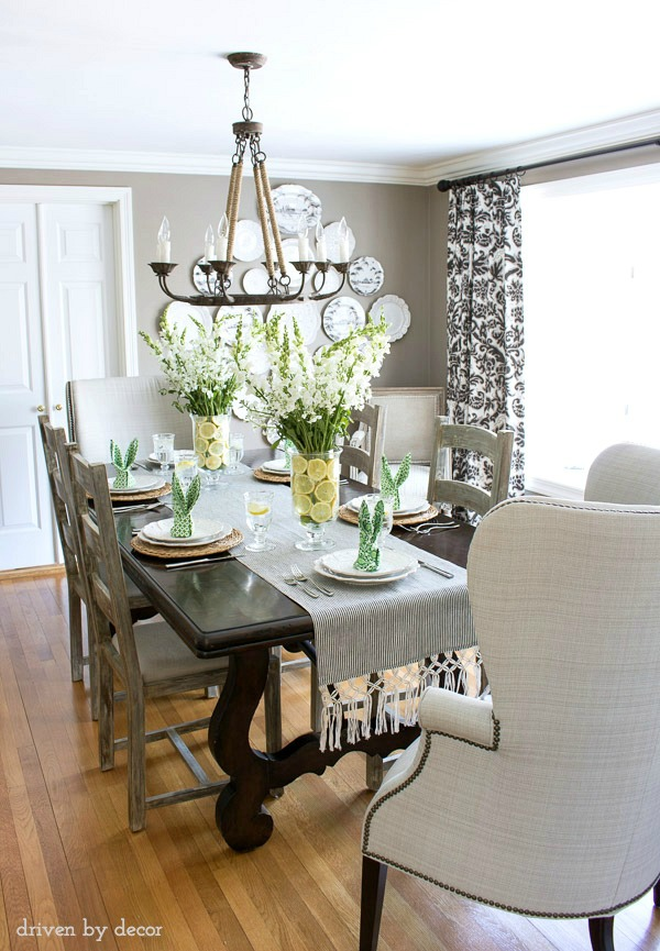 Dining room with simple Easter table decorations - floral centerpieces in vases lined with lemon slices and bunny ear napkins. Great ideas!