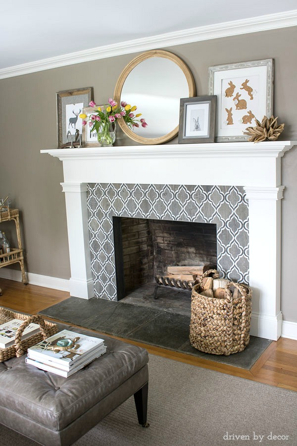 Fireplace decorated for spring! Geometric Walker Zanger tile, round IKEA mirror, art printables, spring tulips, and basket for firewood