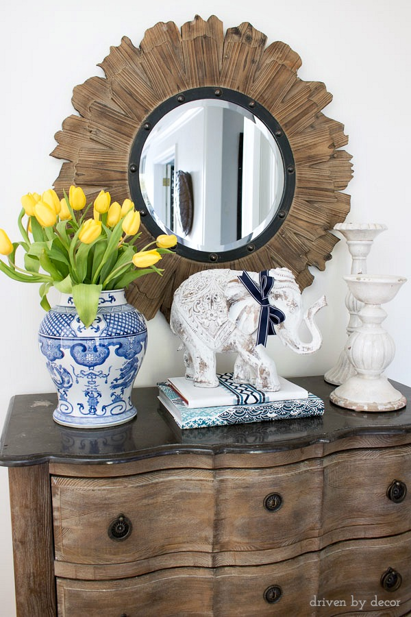 Foyer decor: wood sunburst mirror | blue and white chinoiserie vase with yellow tulips | decorative elephant on fabric-wrapped books | ceramic pillar candleholders | serpentine chest
