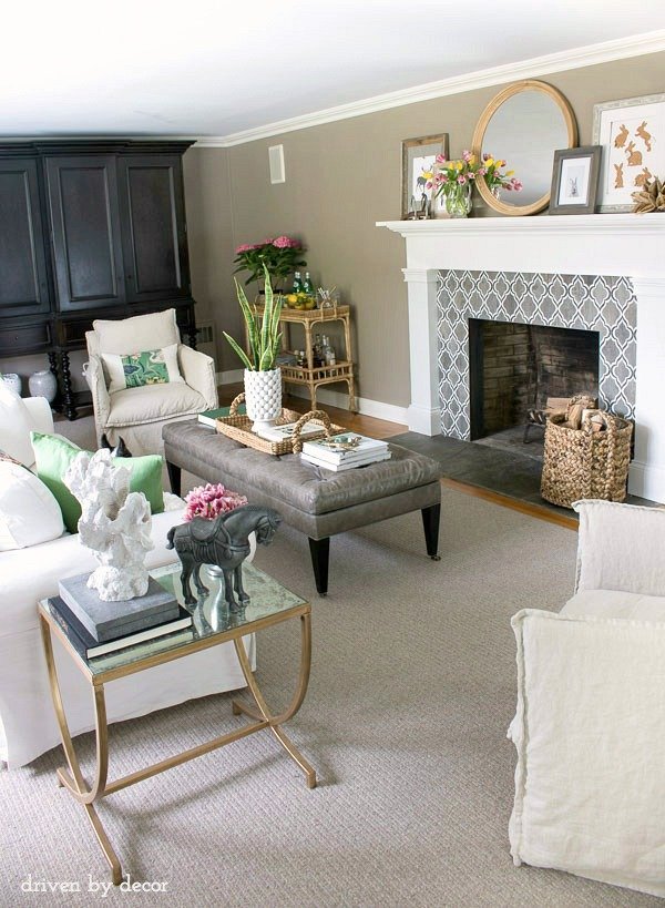 Living Room in Neutrals | Geometric fireplace tile | Layered art and mirror on mantel | Leather ottoman | White IKEA EKTORP sofa | Linen swivel chairs | Rattan bar cart