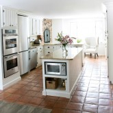 Our New England kitchen with saltillo floors, white planked cabinets, and a cozy brick fireplace
