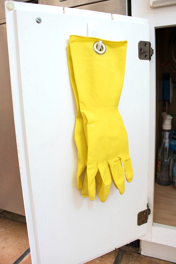 Simple kitchen organization DIY - add grommets to a pair of gloves and hang them on the inside door of your sink cabinet!