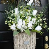 Take a flat-backed basket and fill it with floral foam and faux flowers for the perfect spring door decoration