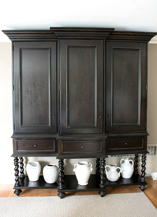 Tall ebony stained china cabinet with spiral legs
