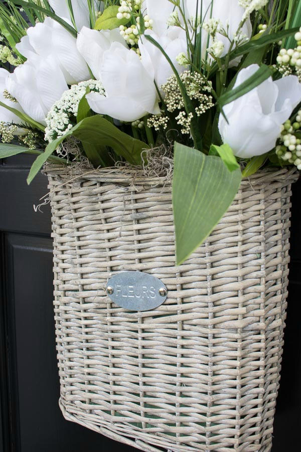 Woven flower basket used to hold faux floral arrangement for a spring door decoration