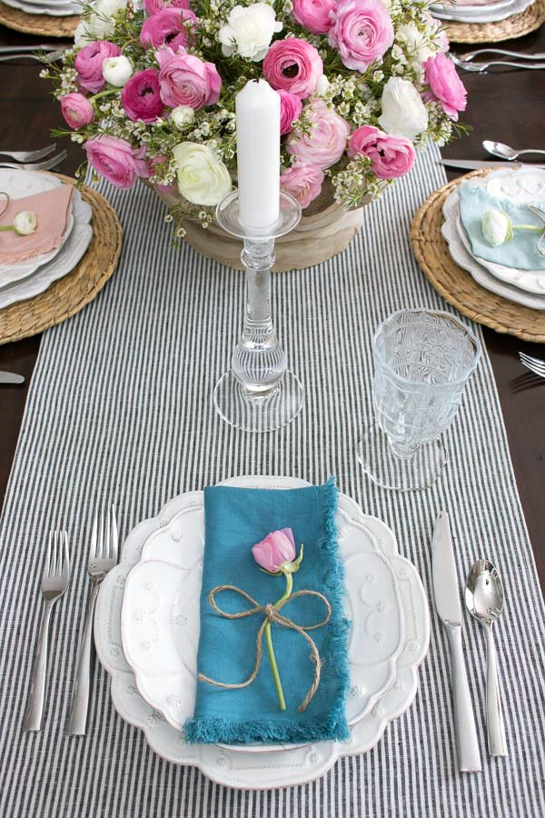 A simple placesetting for a spring tablescape - a single ranunculus tied with twine adorns each plate