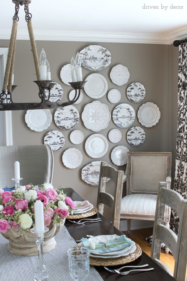Dining room in neutrals with a statement-making plate wall - love the white plates against the dark gray walls!