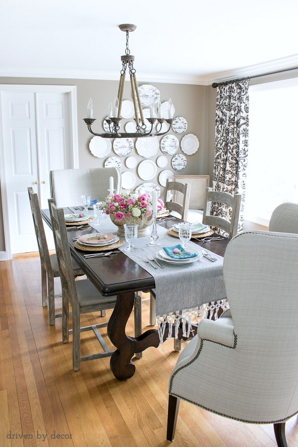 Dining room in neutrals with ladderback side chairs, upholstered wingback end chairs, rope chandelier, and a statement-making plate wall!