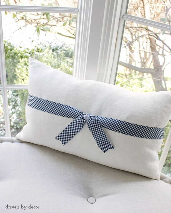 Gingham ribbon tied around a plain linen pillow