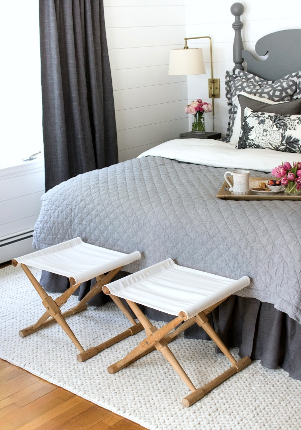 A pair of camp stools at the foot of the bed provides a great spot to stack bed pillows at night and to sit on while getting dressed in the morning!