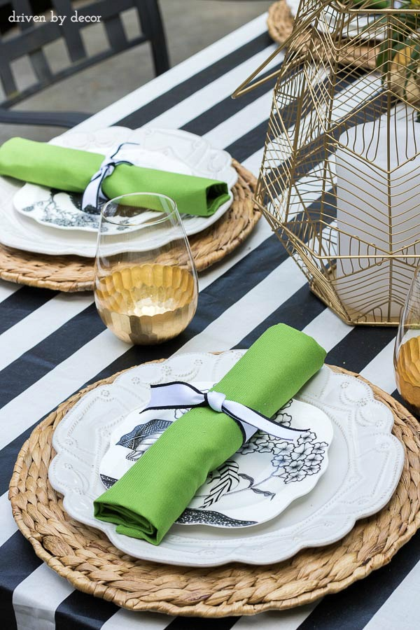 A simple summer placesetting with silverware rolled in napkins an tied with ribbon