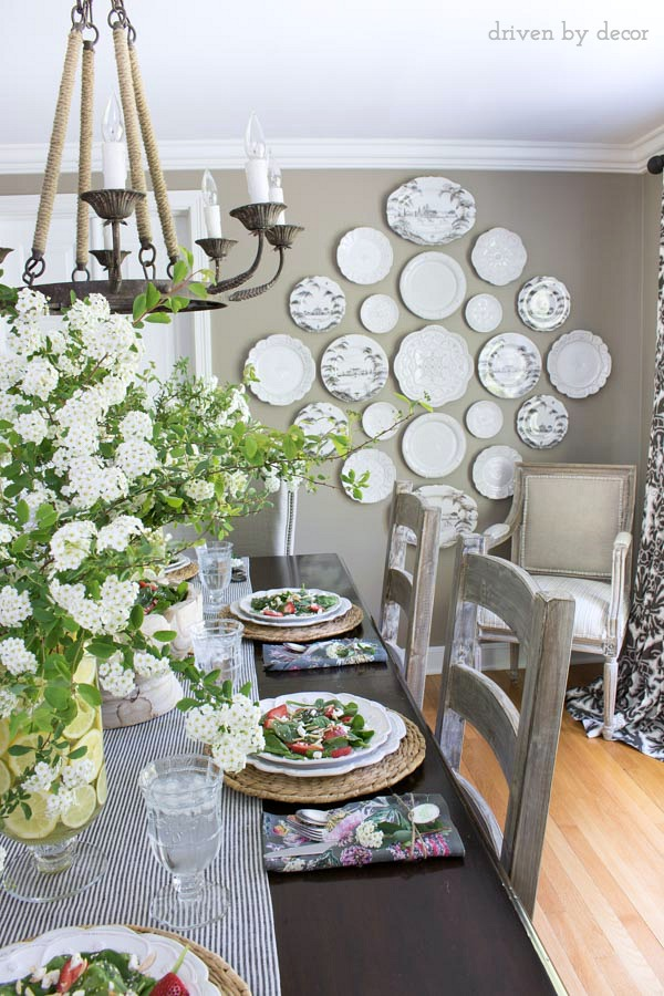 Love the plate wall in this neutral dining room that's decorated for spring