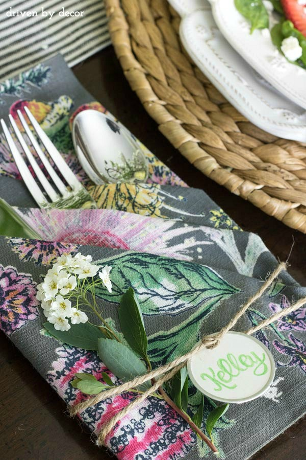 Napkins folded to create pouches for silverware with simple name tags tied on with twine - love!