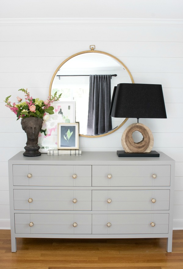 simple styling over a bedroom dresser large round mirror lamp and