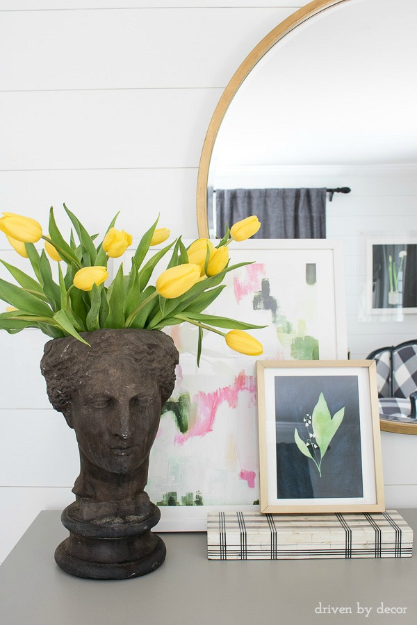 Bust planter, layered art, and a round mirror add style to the top of a bedroom dresser