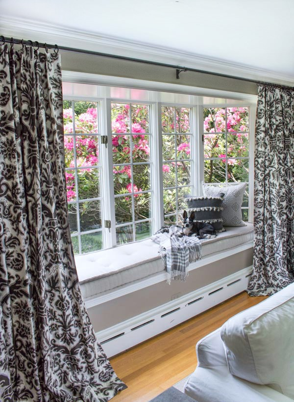Living room window seat with French mattress cushion and blooming azaleas outside