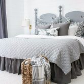 A woven basket at the end of the bed holds extra blankets for chilly nights