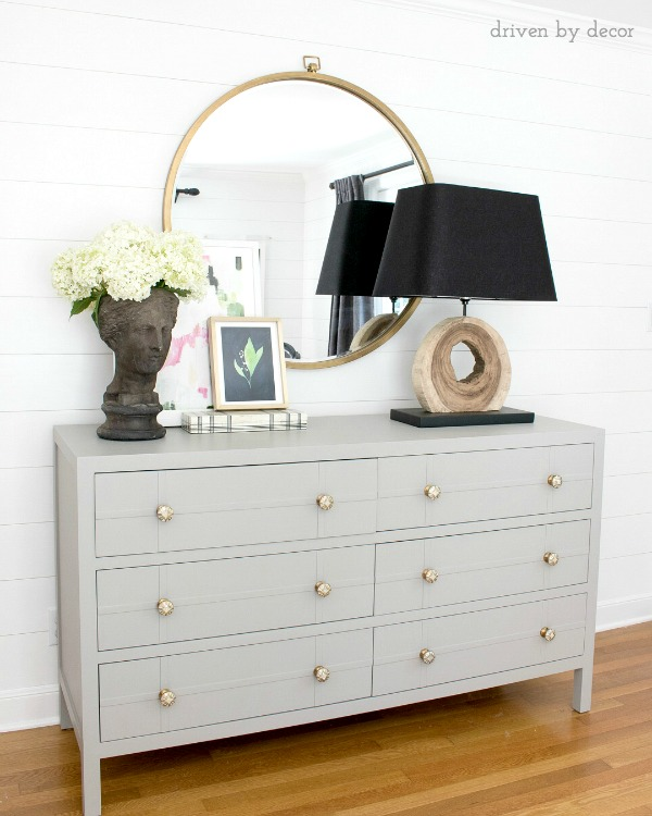 Bedroom dresser with round mirror, layered art, and bust planter filled with summer hydrangeas