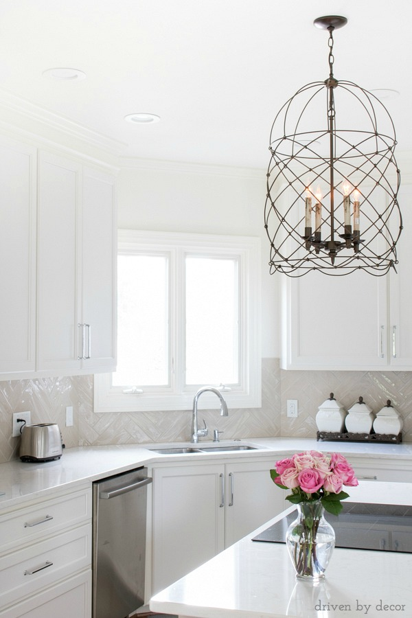 A great example of using a mix of metals in the kitchen - stainless appliances and faucet with bronze lighting