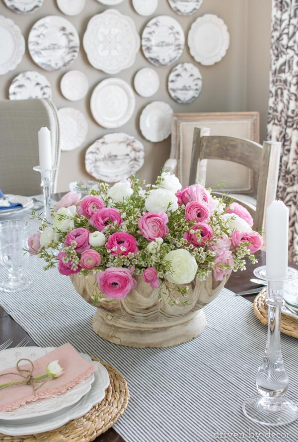 Centerpiece with gorgeous wood scalloped bowl filled with pink and white ranunculus