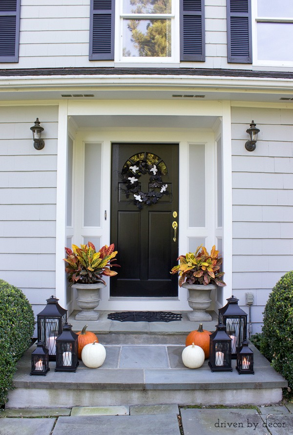 Fall front porch with croton plants, a trio of lantern, and pumpkins