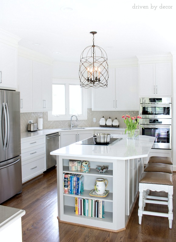 Kitchen with white cabinets, quartz countertop in marble look-alike, wire cage pendant, and large-scale herringbone backsplash. Sources included in post!