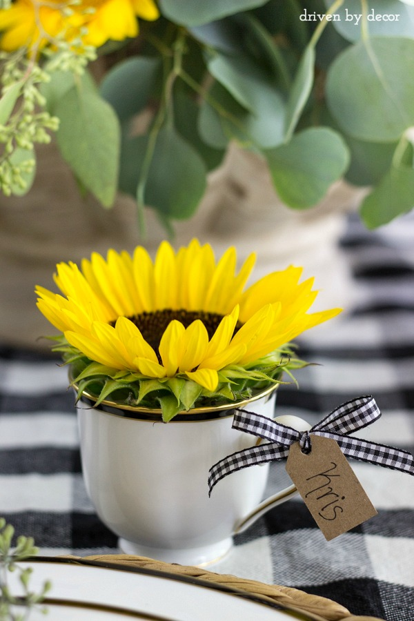 Sunflower in teacup with name tag tied to the handleas a placecard