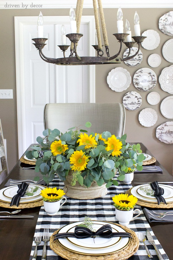 Tall tablescape with sunflowers in a wood bowl, black and white buffalo check table runner and sunflowers in teacups