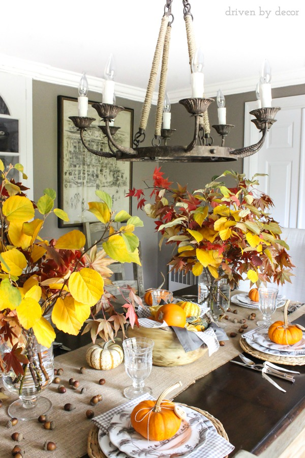 Vases filled with fall branches, scattered acorns, and a wood bowl filled with mini pumpkins were used to create a simple, natural fall tablescape