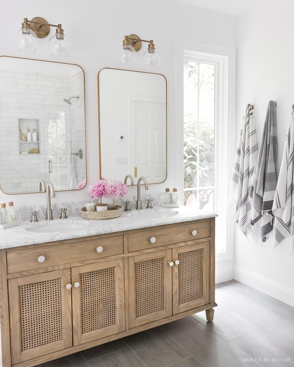 Love the mixed metals in this bathroom design! Brushed nickel faucets and brass / gold mirrors and lights