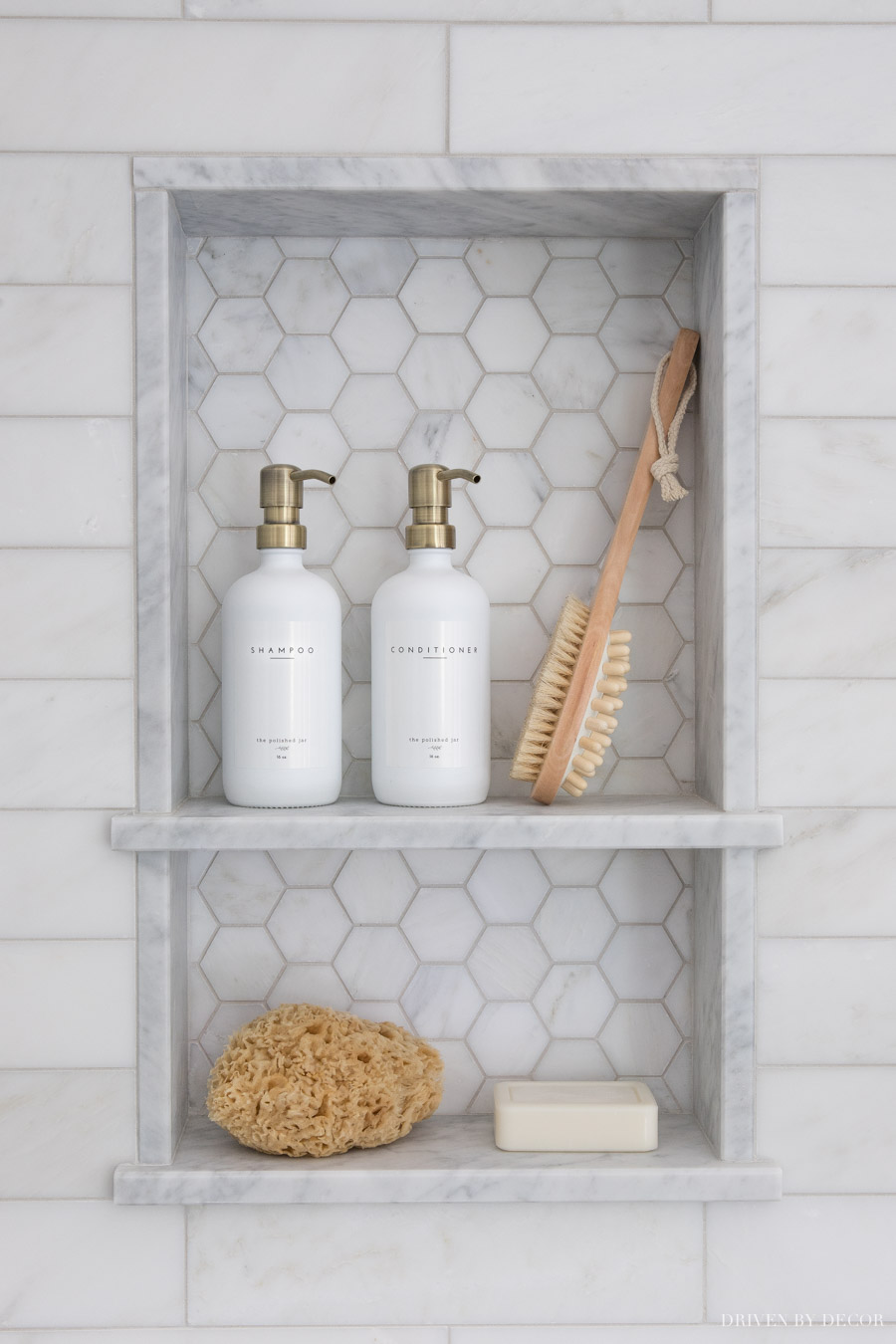 Love the pop of brass with the shampoo pump tops with the satin nickel shower hardware!