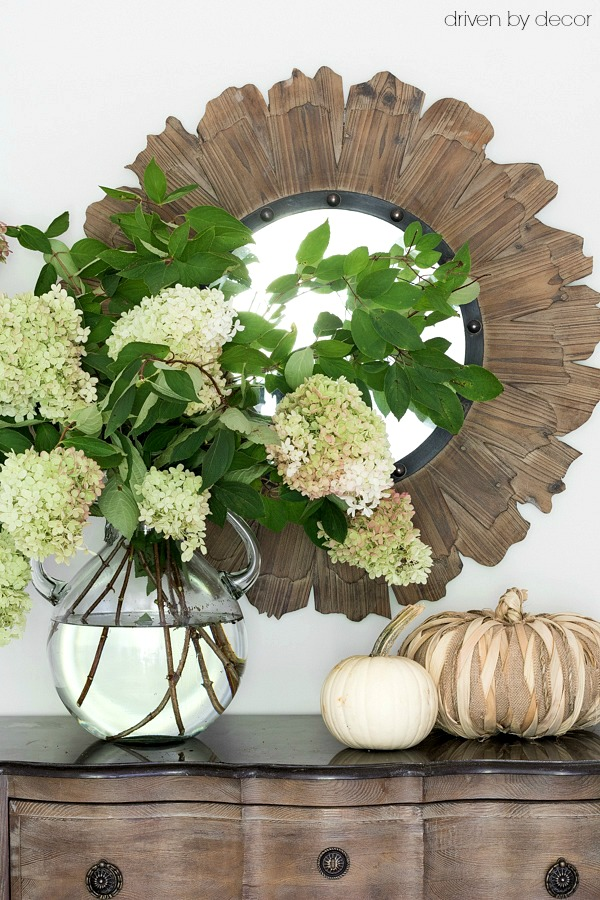 A large glass jug filled with hydrangeas decorates this foyer console for fall