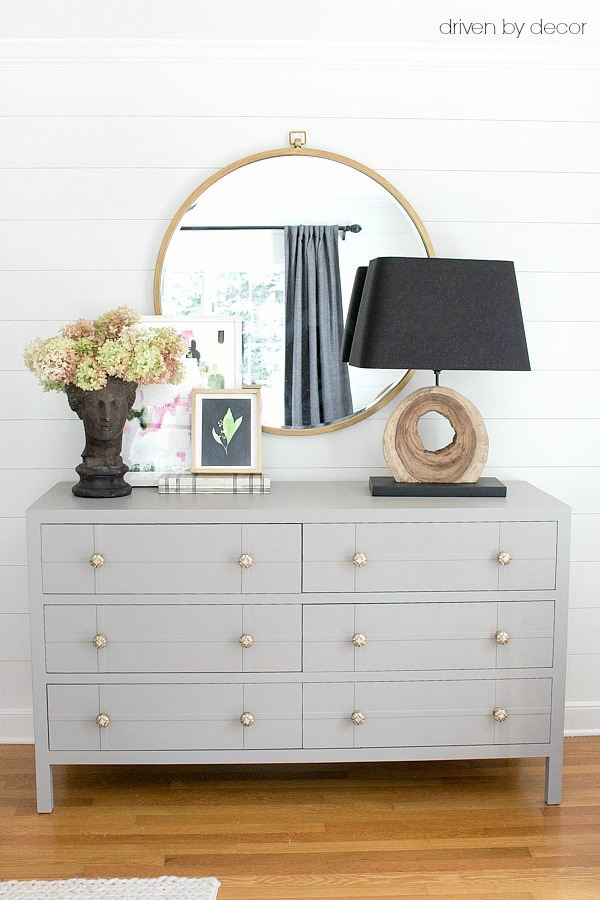 Bedroom dresser painted gray with large round mirror, layered art, and wood slice lamp and shiplap walls