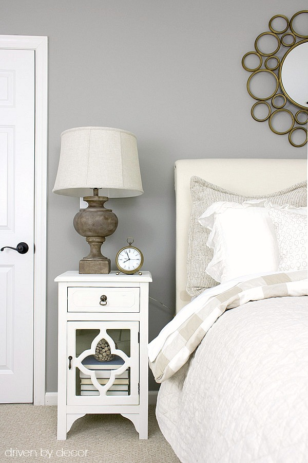 Bedroom nightstand with wood lamp and brass alarm clock in neutrals-filled guest room