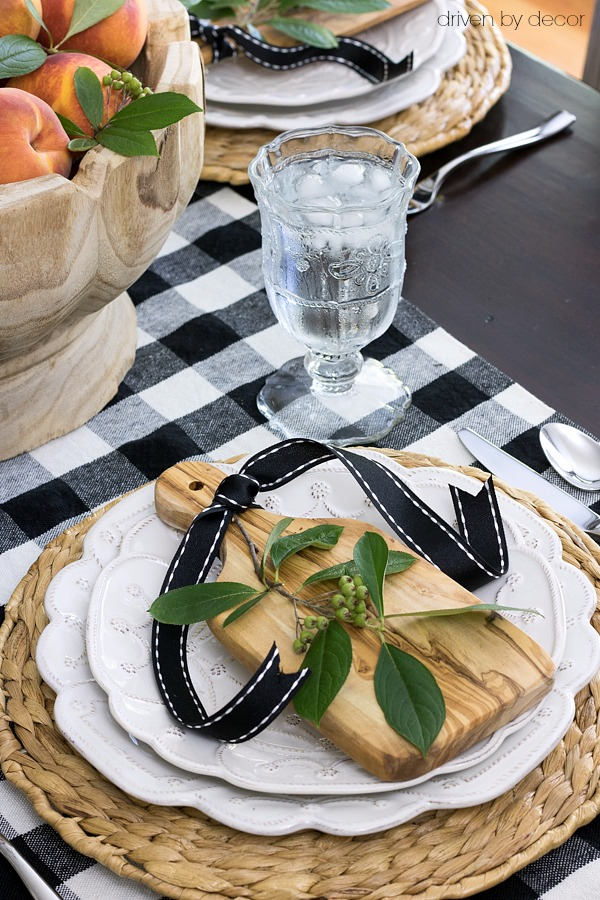 Fall place setting with mini cutting boards, ribbon, and a sprig of greenery on plates with woven chargers.