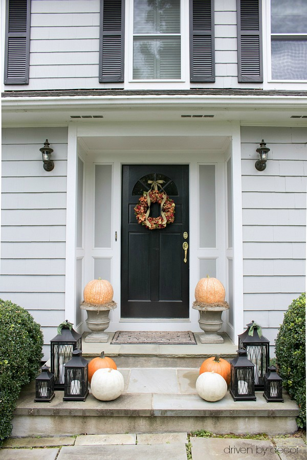 Fall porch with hydrangea wreath, large pumpkins on planters, and a trio of lanterns