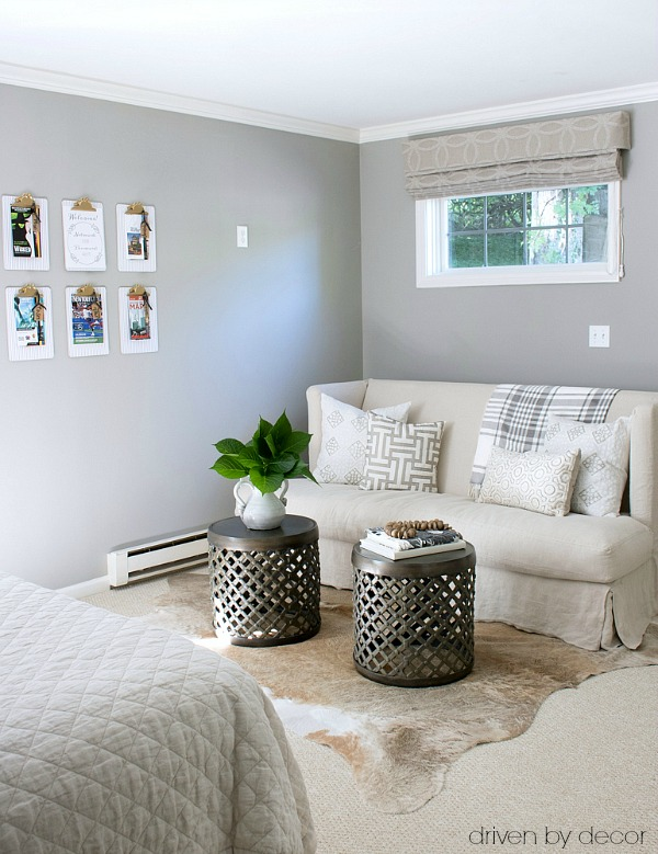Guest room seating area with slipcovered loveseat and twin drum tables