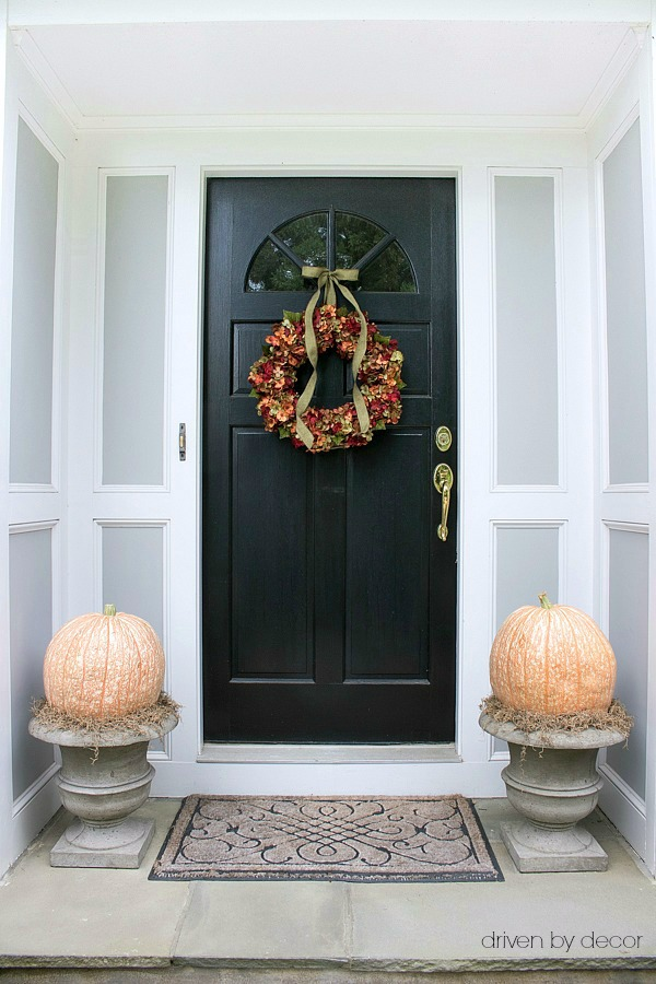 Simple front porch decor - hydrangea wreath and large pumpkins and spanish moss in planters - part of a whole house fall tour